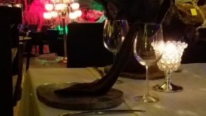 Unique table setting with napkin draped out of the wine glass